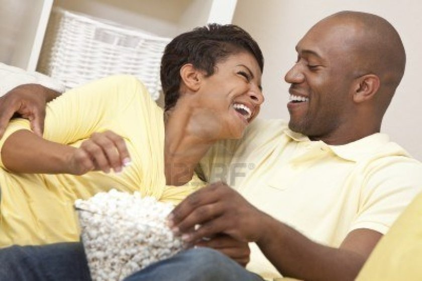 9150707-a-happy-african-american-man-and-woman-couple-in-their-thirties-sitting-at-home-laughing-eating-popc